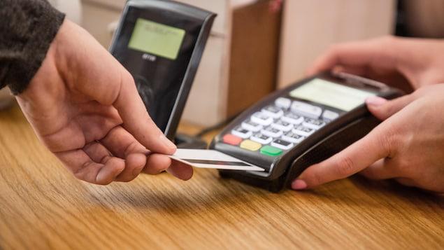 Une personne tend sa carte vers une machine à paiement direct.