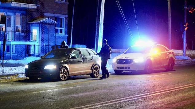 Un policier est devant un véhicule et une jeune femme semble chercher un document.