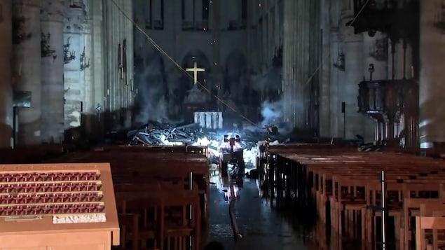 L'intérieur de l'église après le feu. Dans la nef, des débris s'accumulent.