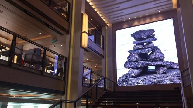 Une murale décorative représentant une sculpture, surplombant un escalier dans le navire de croisière de luxe Viking Sea, dans le port de Montréal.