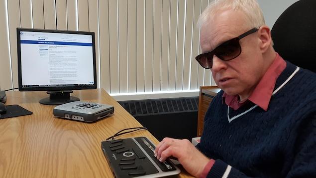 René Binet, une personne aveugle, est assis à un bureau. Il consulte un site internet à l'aide d'une plage braille.