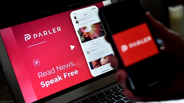Un téléphone intelligent et un ordinateur portable affichent la page d'accueil du réseau social Parler.
