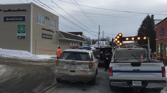 Des véhicules d'urgence près d'un commerce.