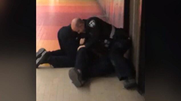 Deux inspecteurs tentent d'immobiliser un jeune homme au sol, dont on ne voit que les jambes et les pieds.