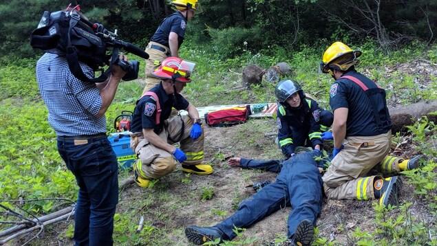 Une caméraman filme la reconstitution d'un accident en forêt.