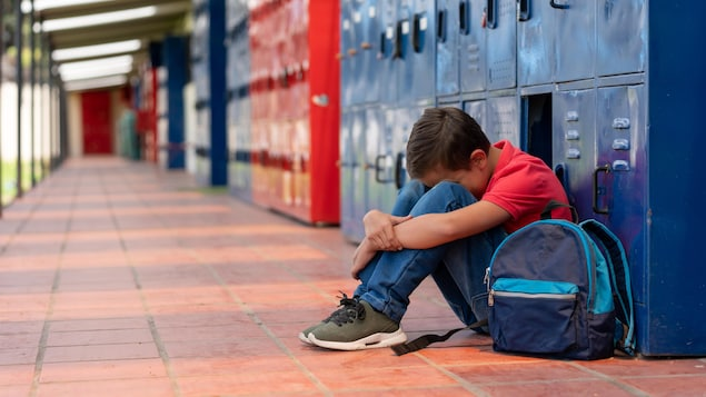 Un enfant assis par terre la tête entre les genoux et le dos à des casiers dans le corridor d'une école.