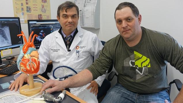 Le médecin Mario Sénéchal derrière un bureau avec son patient David Labrie, qui tient un coeur artificiel.