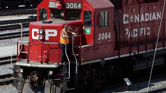 Un travailleur debout  près de la cabine du conducteur de la locomotive d'un train du Canadien Pacifique.