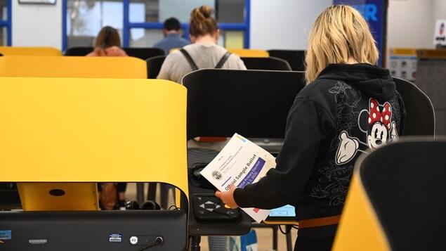 Des gens vus de dos votent dans un local blanc.