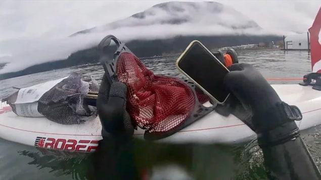 Un plongeur place un téléphone intelligent dans un filet sur un bateau.