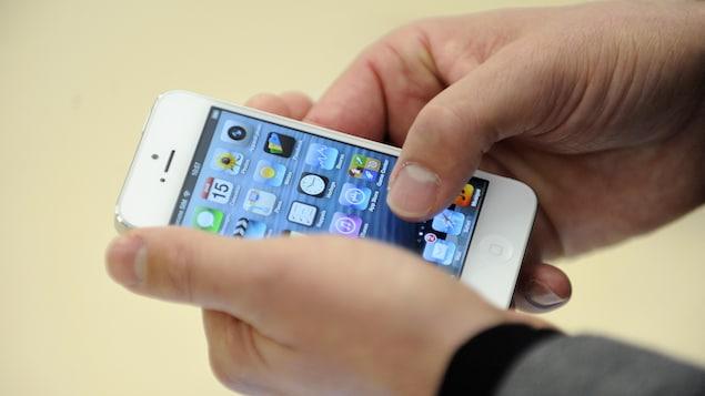 Des mains tiennent un iPhone 5.