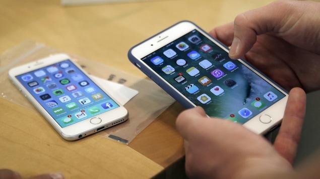 Plan rapproché des mains d'une personne manipulant un iPhone 7 Plus, alors qu'un iPhone 6 est posé sur une table en arrière-plan.