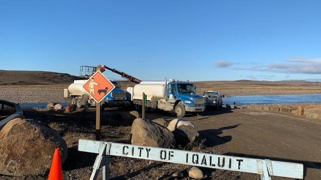 Des camions-citernes s'approvisionnent en eau au bord de la rivière Sylvia Grinnell, à Iqaluit.