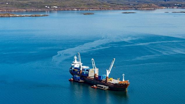 Un navire en mer, au large d'Iqaluit, avec des barges et des conteneurs.