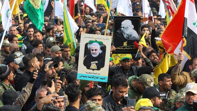 Une foule d'hommes des portraits du général Soleimani et brandissant des drapeaux de milices pro-iraniennes en Irak.