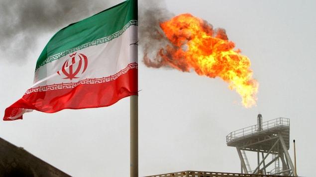 Un drapeau iranien flotte devant une cheminée crachant des flammes vers le ciel, sur la réserve de pétrole Soroush, près du golfe Persique, en Iran.