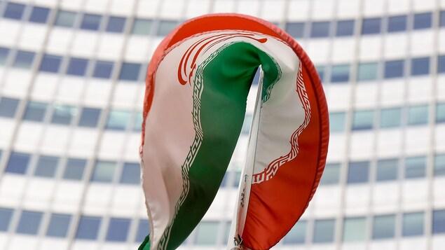 Le drapeau iranien flotte au vent devant un immeuble.