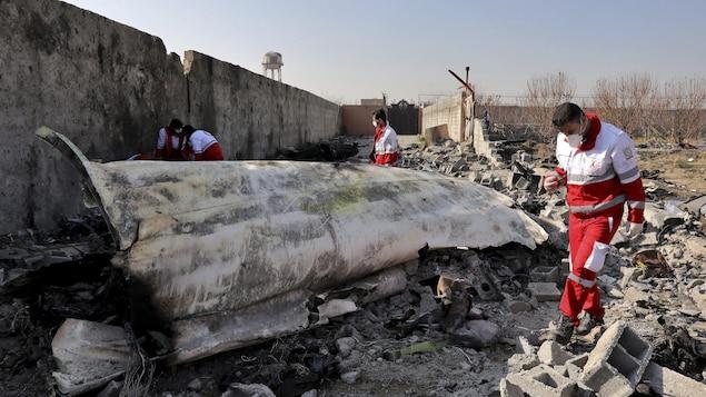 Des membres de l'équipe de secours cherchent dans les débris de l'avion.