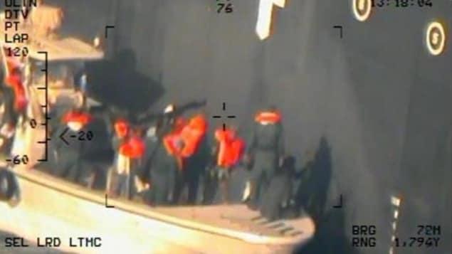 Des hommes portant des gilets sur une frégate près d'un bateau.