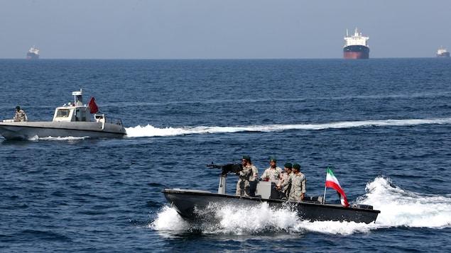 Des soldats iraniens sont dans un hors-bord monté d'un drapeau iranien. Un pétrolier navigue en arrière-plan.