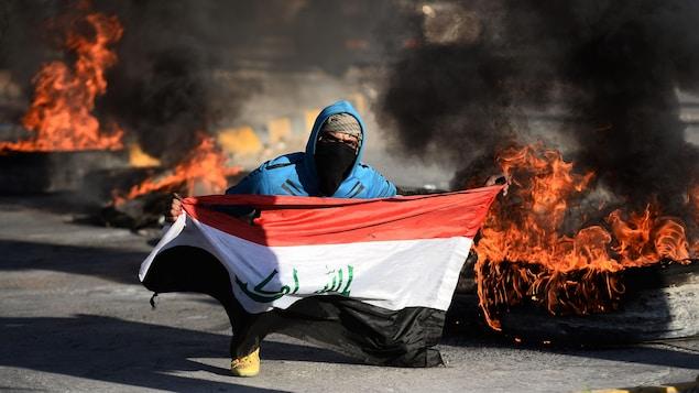 Un protestant irakien tient un drapeau dans un décor enflammé.