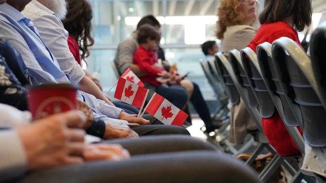 Des gens assis sur une chaise tiennent des drapeaux du Canada.
