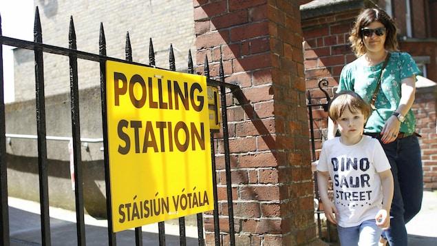 Une femme quitte un bureau de vote sur le référendum au sujet de l'avortement en Irlande.