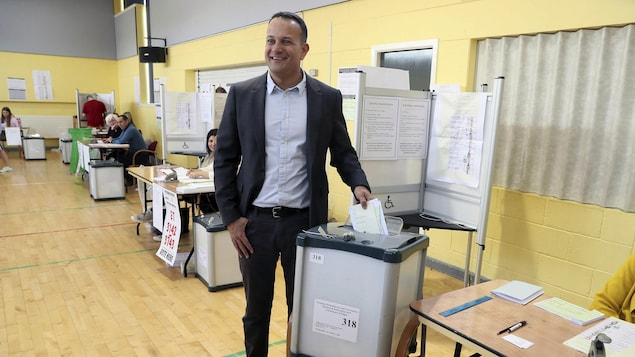Un politicien irlandais dépose un bulletin de vote dans une urne.