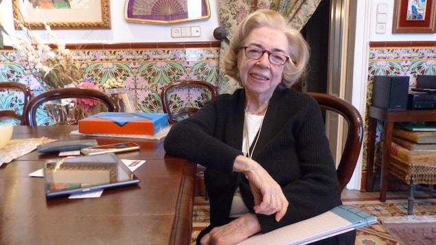 La dame est assise dans sa salle à manger. Il y a une tablette et un téléphone cellulaire sur la table.