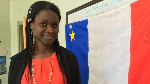 Isabelle Dasylva-Gill devant un drapeau acadien.