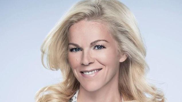 Une femme blonde sourit.