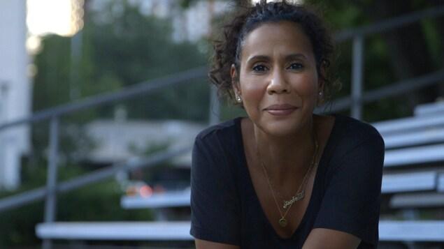 Une femme assise dans une estrade regarde l'objectif en esquissant un léger sourire.