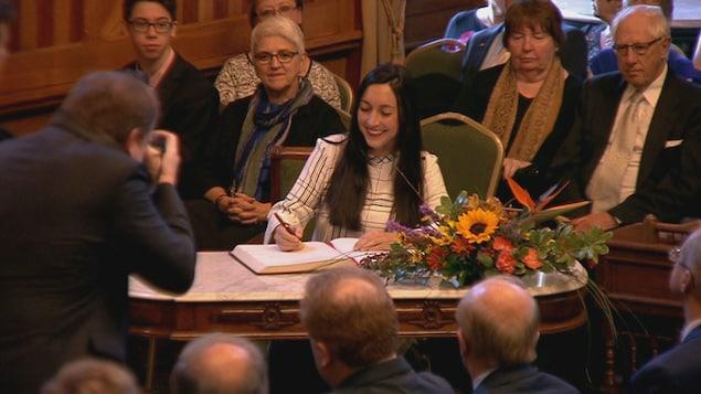 Isabelle Thériault signe un document.