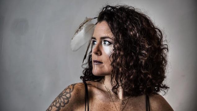 La femme arbore un maquillage original et une plume d'aigle aux cheveux.