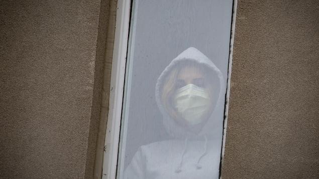 Une jeune femme regarde à travers la fenêtre d'un hôpital, portant un masque.