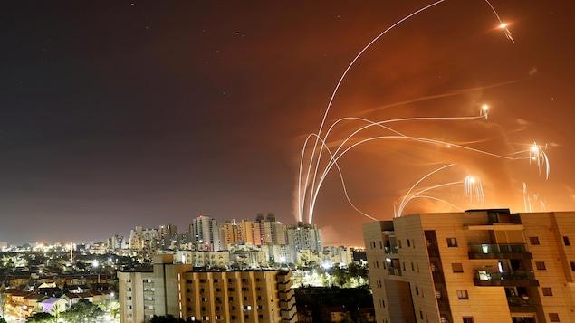 Des lueurs de roquettes au-dessus d'un ensemble d'immeubles.