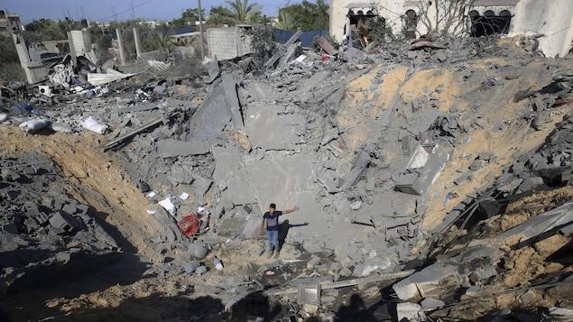 Un jeune Palestinien, dans le cratère fait par un missile israélien, où se trouvait une maison à Al-Qarara, dans la bande de Gaza.