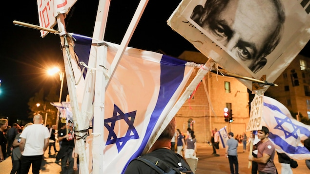 Des manifestants dans la nuit avec des drapeaux israéliens.