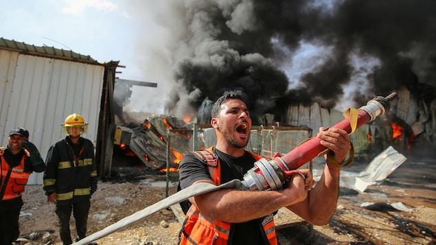 Un pompier palestinien participe aux efforts pour éteindre un incendie, le lundi 17 mai 2021.