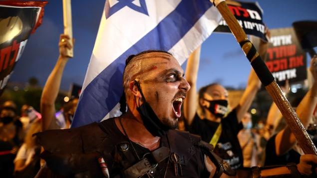 Un manifestant au visage bariolé et brandissant un drapeau israélien.