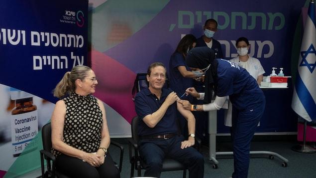 Relevant sa manche, Isaac Herzog se fait vacciner aux côtés de son épouse.