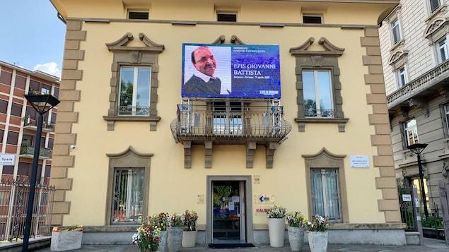 Un écran posé sur un balcon affiche les noms et photos des victimes de la COVID.
