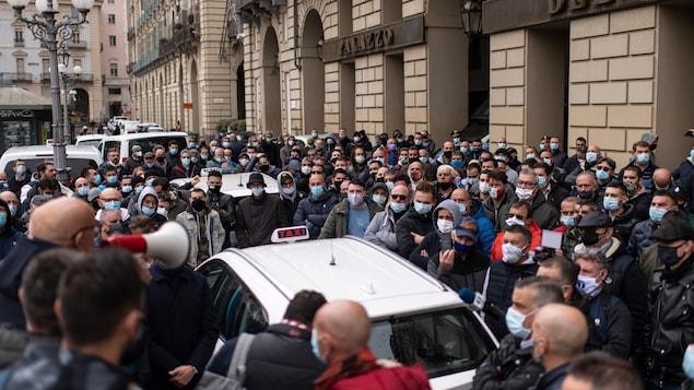 Des dizaines de personnes masquées sont rassemblées sans grande distanciation physique autour de taxis. Un homme s'adresse à eux avec un mégaphone.