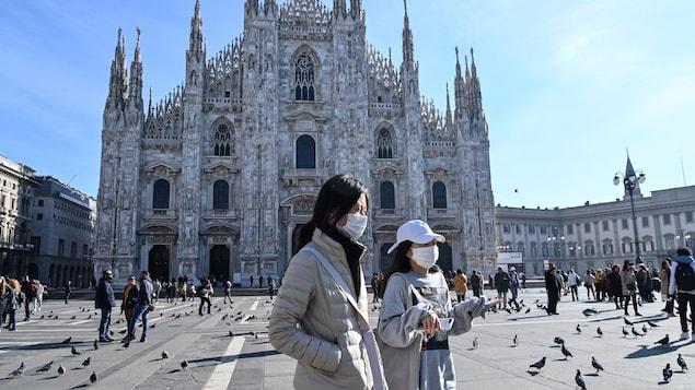 Deux femmes masquées marchent devant la cathédrale de Milan.