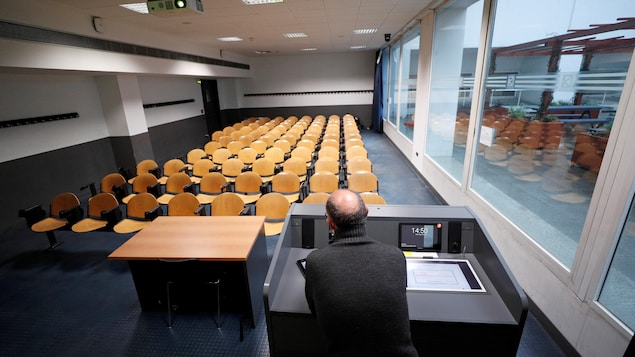 Un professeur est vu de dos devant une classe vide.