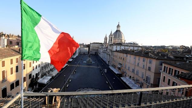 Un drapeau italien flotte au vent sur une terrasse à Rome