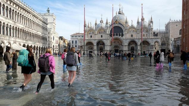 Des touristes marchent à Venise sur la place Saint-Marc inondée.