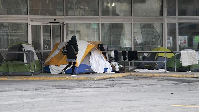 Des tentes installées dehors près d'un édifice.