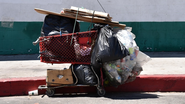 Un panier d'épicerie sur le bord du trottoir. Il est rempli de sacs et d'effets personnels appartenant à une personne sans abri.