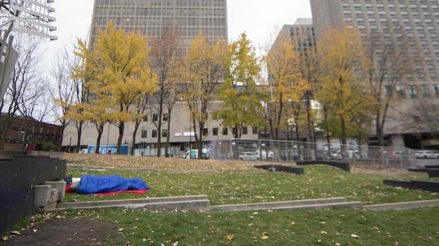 Une personne dort dans un parc à Montréal.